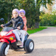 Foto de Stock  : Adorable little girls riding on kid's motobike in green park