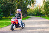 Adorable little girls riding on kid's motobike in the green park — Photo