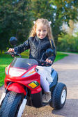 Adorable happy little girl in leather jacket sitting on her toy motorcycle — Stock Photo