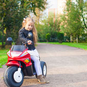 Little adorable rock girl in leather jacket sitting on her toy motorcycle — Stock Photo