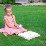Adorable little girl holding green Easter egg sitting outdoor — Stock Photo #40575021