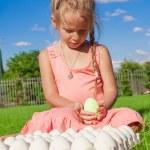 Adorable little girl holding green Easter egg sitting outside — Stock Photo #40575049