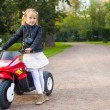 Foto de Stock  : Beautiful little girl having fun on her toy motorcycle outdoors