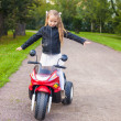 Foto de Stock  : Little beautiful rock girl in leather jacket on her bike