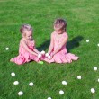 Foto de Stock  : Two adorable little girls playing with Easter Eggs in yard