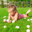 Foto de Stock  : Little happy girl playing with white Easter eggs on green grass