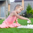 Foto de Stock  : Little beautiful girl is preparing for Easter with tray of white eggs