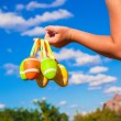 Foto de Stock  : Closeup hand of little girl holding colorful Easter eggs background blue sky