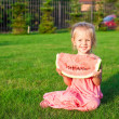 Little girl with big piece of watermelon in hands on green grass — Stock Photo #40575315