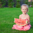 Little girl with big piece of watermelon in hands on green grass — Stock Photo #40575361