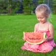 Little girl with big piece of watermelon in hands on green grass — Stock Photo #40575365