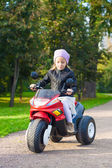Little adorable girl having fun on her toy motorcycle — Stock Photo
