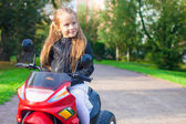 Portrait of happy little rock girl in leather jacket sitting on her toy motorcycle — Stock Photo