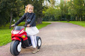 Beautiful little girl having fun on her toy motorcycle outdoors — Stock Photo