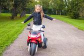 Little beautiful rock girl in leather jacket on her bike — Stock Photo