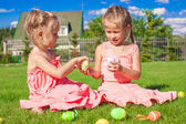 Adorable little girls playing with Easter Eggs on green grass — Stock Photo