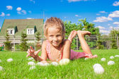 Little adorable girl playing with white Easter eggs in the yard — Stock Photo