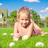 Portrait of little cute girl playing with white Easter eggs on green grass — Stock Photo