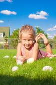 Portrait de petite fille mignonne, jouant avec pâques blanc d'oeufs sur l'herbe verte — Photo
