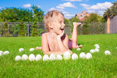 Little happy girl playing with white Easter eggs on green grass — Stockfoto