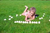 緑の草に卵の白イースターで遊んで幸せな少女 — ストック写真