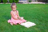 Adorable little girl holding green Easter egg sitting outdoor — Stock Photo