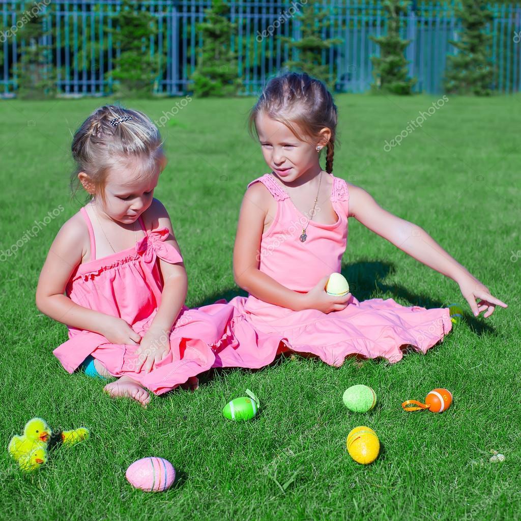 两个可爱的小女孩玩在绿色草地上的复活节彩蛋