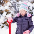 Little girl playing with red shovel in the garden on winter day — Stock Photo
