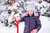 Little girl playing with red shovel in the garden on winter day — Fotografia Stock
