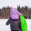 Little girl riding on young father outdoors in cold winter day — Stock Photo