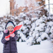 Little girl playing with red shovel in the garden — Stock Photo