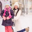 Happy adorable little girl and young mother ice-skating — Stock Photo