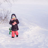 Little girl goes sledding on a warm winter day — Stock Photo