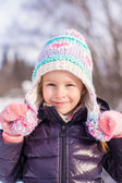 Portrait of little adorable girl in winter hat at snowy forest — Stock Photo