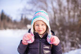 Portrait of little adorable girl in winter hat at snowy forest — Photo