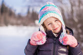 Portrait of little adorable girl in winter hat at snowy forest — Foto Stock