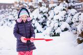 Bambina giocando con pala rossa nel giardino — Foto Stock