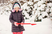 Little adorable girl play with snow shoveling on a winter day — Foto de Stock