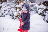 маленькая девочка играть с снег лопатой на зимний день — Стоковое фото