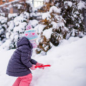 Little adorable girl play with snow shoveling on a winter day — Stock Photo