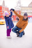 Young father and adorable little girl have fun on skating rink — Стоковое фото