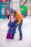 Little happy girl with young father have fun on skating rink — Стоковое фото