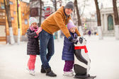 Little girls with young father enjoying skating — Stock Photo