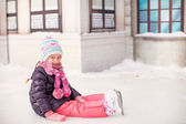Adorable little girl sitting on ice with skates after the fall — Stock Photo