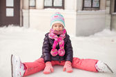Little adorable girl sitting on ice with skates after the fall — Stock Photo