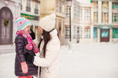 Adorable little girl and her young mother on a skating rink — Stock Photo