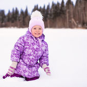 Little happy adorable girl sitting on the snow at winter sunny day — Stockfoto