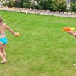Two little adorable girls playing with water guns in the yard — Stock Photo #41243809