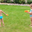 Two little adorable girls playing with water guns in the yard — Stock Photo #41243859