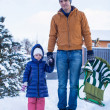 Stock Photo: Young dad and little girl go sledding in a cold winter day